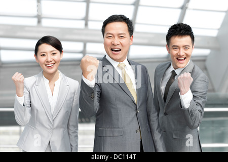 Cheerful business team punching the air at the airport - Stock Photo