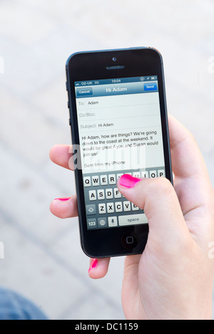 Woman sending an email on Apple iPhone 5 - Stock Photo