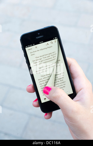 Woman turning virtual page of an ebook with the Apple iBooks app on an iPhone 5 - Stock Photo