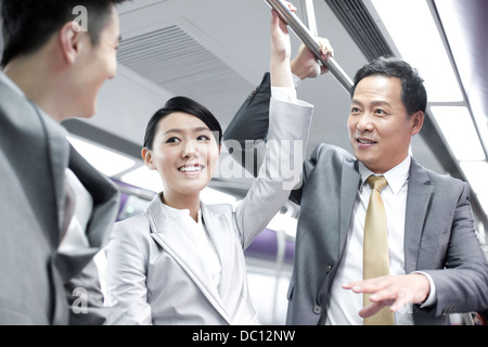 Business persons talking in subway train - Stock Photo