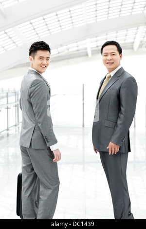 Confident business people in airport lobby - Stock Photo