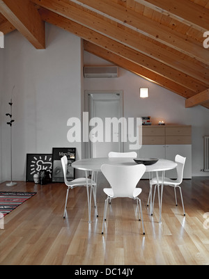Modern Dining Room With Wood Floor In The Mansard Near To Main Door