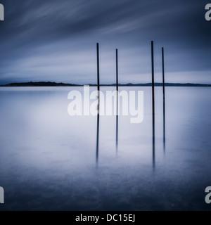Posts in water at dusk, Stegelholmen, Gothenburg, Sweden - Stock Photo