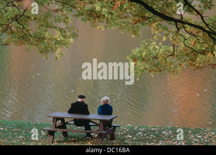 Seniors on a park bench enjoy fall colors reflected in the water, Ontario, Canada  Early autumn, Maple tree overhead - Stock Photo