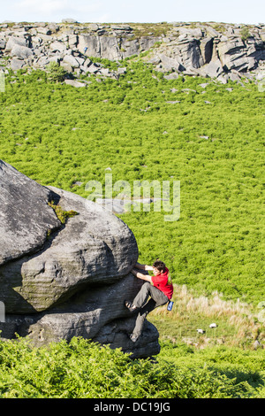 a man in a red t-shirt climbing and bouldering at Burbage Valley in the Peak District National Park near Sheffield, - Stock Photo