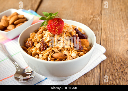 Musli (granola) close up with strawberry, dry fruits, nuts and cereals in white bowl on wooden background (table). - Stock Photo