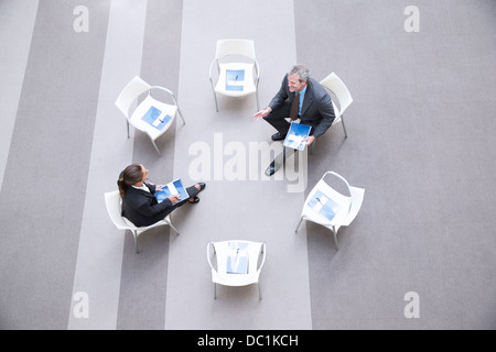 High angle view of businessman and businesswoman talking at chairs in circle - Stock Photo