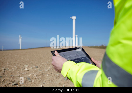 Project manager using digital tablet in front of wind farm - Stock Photo