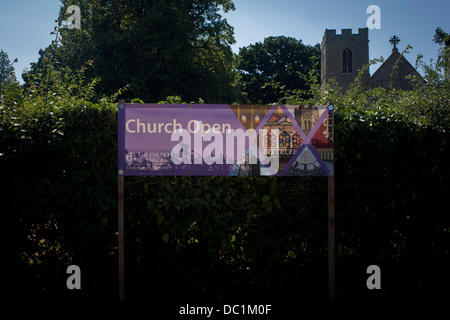 Church Open banner on display outside the flint wall architecture of St Michael's Anglican church at Irstead, on - Stock Photo