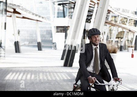 Mid adult businessman riding bicycle in city - Stock Photo