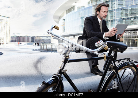 Mid adult businessman using digital tablet in city - Stock Photo
