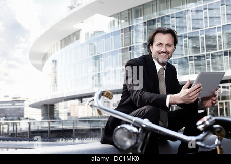 Mid adult businessman using digital tablet in city, portrait - Stock Photo