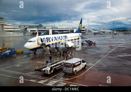 Passengers board a Ryanair flight at a rainy Dublin Airport ireland - Stock Photo