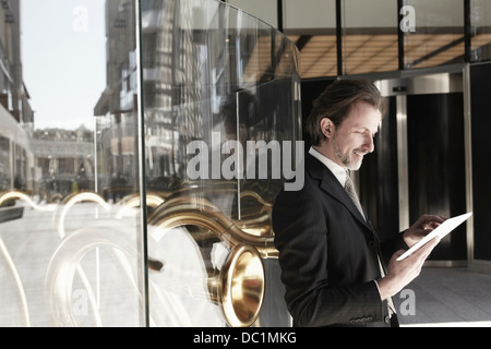Mid adult businessman leaning against store window and using digital tablet - Stock Photo