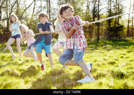 Group of young children playing tug o war - Stock Photo