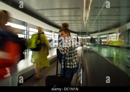 Passengers on Travelator at Dublin airport terminal one - Stock Photo