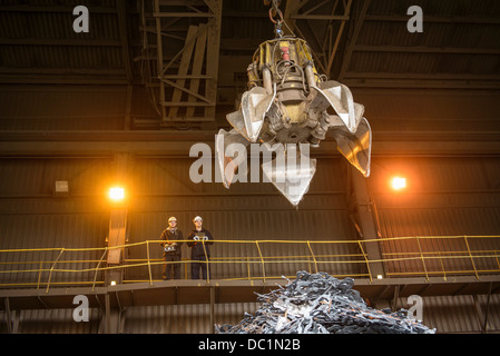 Steel workers overseeing mechanical grabber in steel foundry - Stock Photo