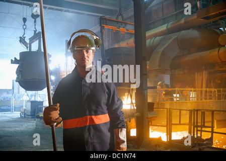 Portrait of steel worker in steel foundry - Stock Photo