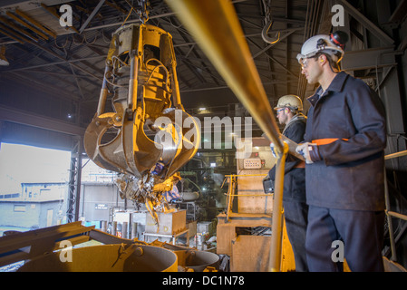 Workers watching mechanical grabber in steel foundry - Stock Photo