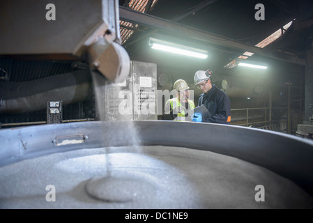 Workers monitoring container of steel shot in steel foundry - Stock Photo