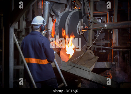 Steel worker pouring molten metal in steel foundry