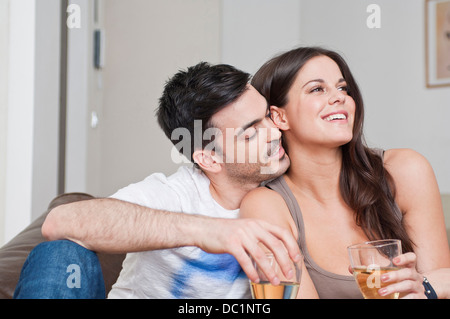 Young couple sitting on sofa sharing glass of wine - Stock Photo