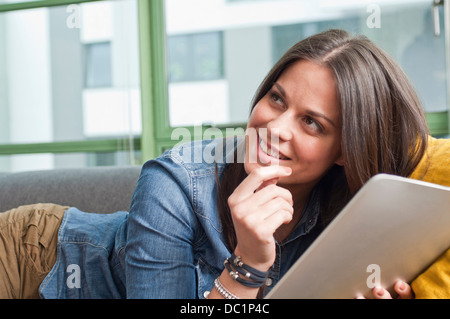 Close up of young woman lying on sofa holding digital tablet - Stock Photo