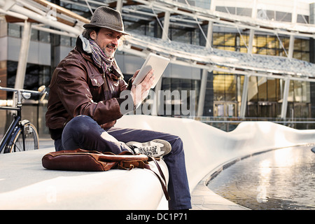 Mid adult man using digital tablet in city - Stock Photo