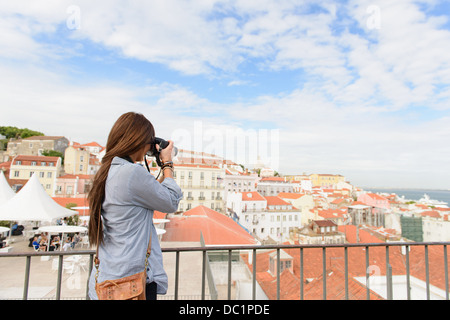 Young female tourist photographing in Alfama District, Lisbon, Portugal - Stock Photo