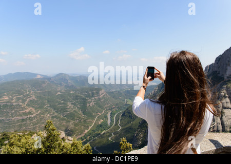 Young female tourist photographing the view of montserrat, Spain - Stock Photo