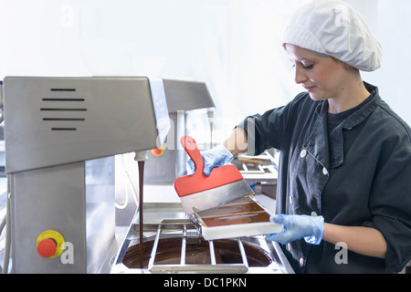 Chocolatier smoothing chocolate in moulds - Stock Photo