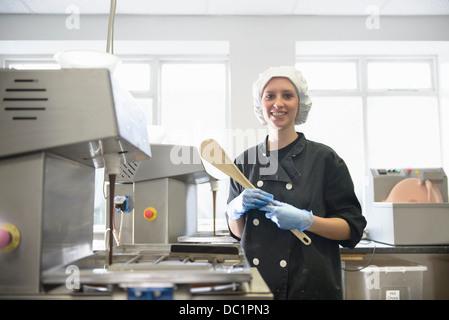 Portrait of chocolatier in sweet factory - Stock Photo