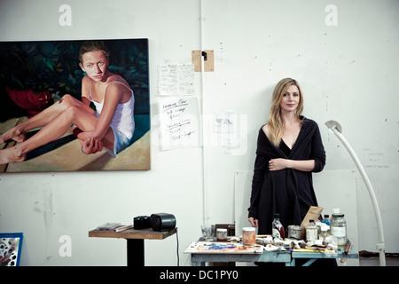 Mid adult woman standing in artist's studio, portrait - Stock Photo
