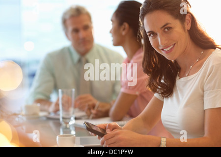 Portrait of smiling businesswoman with cell phone in meeting - Stock Photo