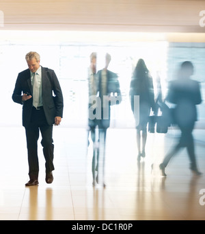 Businessman checking cell phone in lobby - Stock Photo