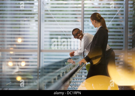 Smiling businessman and businesswoman talking in office - Stock Photo
