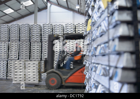 Forklift truck moving stock in warehouse - Stock Photo