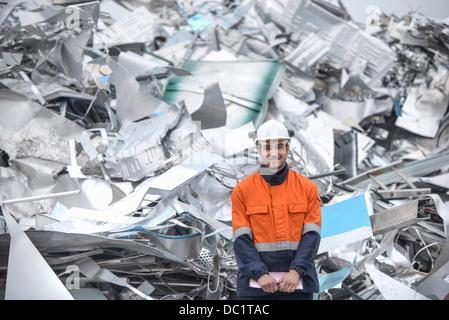 Portrait of worker in front of scrap aluminum - Stock Photo