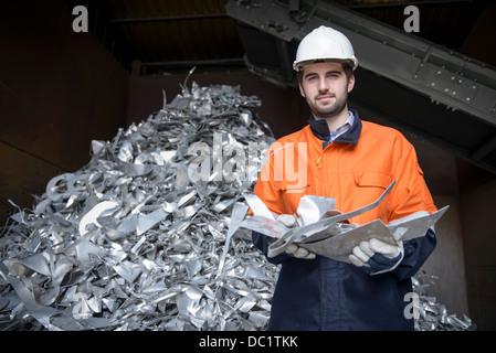 Portrait of worker holding scrap aluminum - Stock Photo