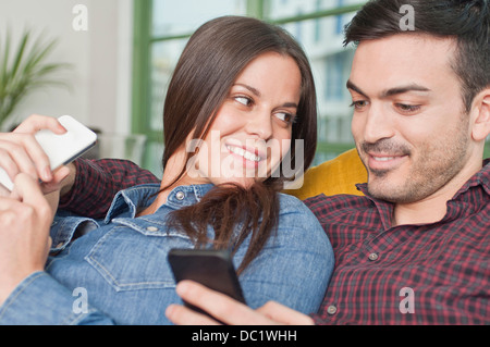 Young couple at home using mobile phones - Stock Photo