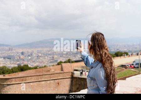 Young female tourist photographing view of Barcelona city, Spain - Stock Photo