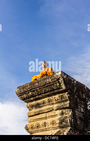 Young Buddhist monk sitting outside temple in Angkor Wat, Siem Reap, Cambodia - Stock Photo