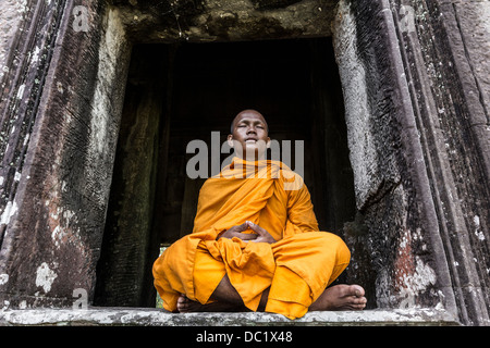 Young Buddhist monk meditating in temple in Angkor Wat, Siem Reap, Cambodia - Stock Photo