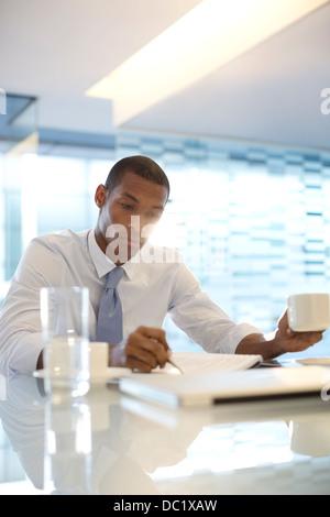 Serious businessman reading paperwork - Stock Photo