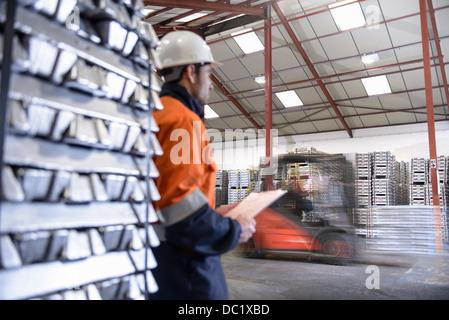 Warehouse workers moving stacked aluminum ingots - Stock Photo