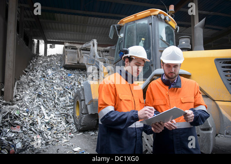 Workers checking clip chart in scrap metal yard - Stock Photo