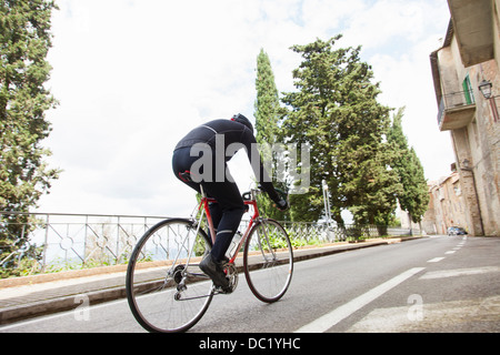 Cyclist riding up road in Umbria, Italy - Stock Photo