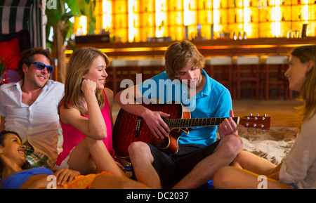 Young man playing guitar to friends in bar - Stock Photo