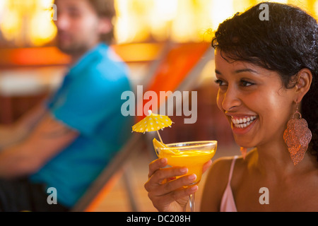 Close up of young woman holding cocktail at indoor beach party - Stock Photo