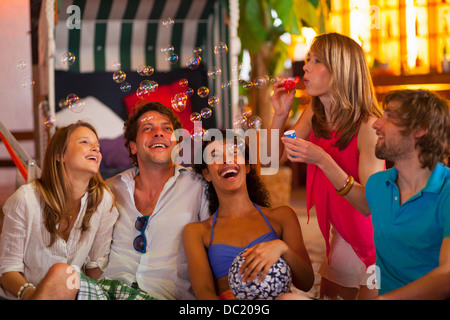 Group of friends blowing bubbles at indoor beach party - Stock Photo